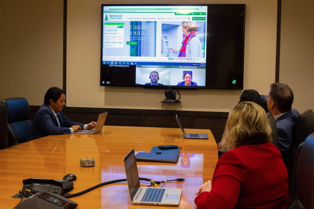 Redwood Credit Union programming manager Ken Kondo, seated at left, and his colleagues demonstrate the bank's video conferencing abilities which also allows screen sharing with employees telecommuting from their homes, amidst the COVID-19 coronavirus pandemic, at the RCU main office in Santa Rosa, California, on Thursday, March 12, 2020. (Alvin Jornada / The Press Democrat)