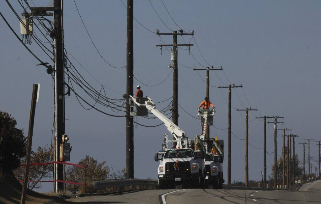 FILE - In this Nov. 25, 2018 file photo Utility crews repair overhead lines along Pacific Coast Highway just west of Malibu, Calif., where the Woolsey Fire burned down from the Santa Monica Mountains to the water's edge at Leo Carrillo State Beach. Southern California Edison announced in its quarterly earnings report that its equipment probably caused the November 2018 Woolsey Fire that raged from north of Los Angeles through Malibu to the sea, killing three people and burning more than 1,600 homes and other buildings. (AP Photo/John Antczak,File)