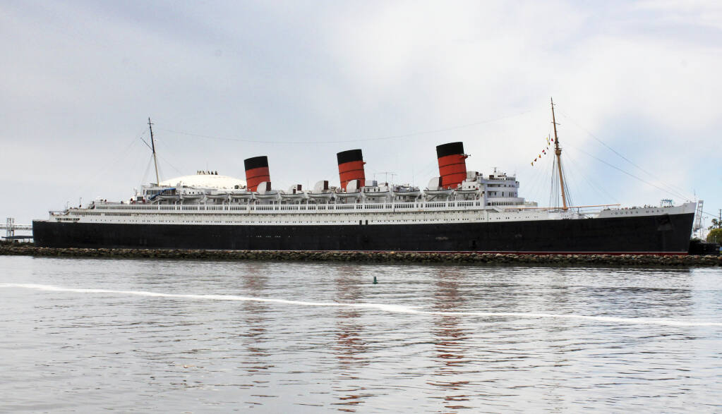 FILE - This May 15, 2015 file photo shows the retired Cunard ocean liner Queen Mary, at its permanent mooring in the harbor at Long Beach, Calif. City officials in Long Beach have said they will spend $2.5 million to maintain the historic Queen Mary ocean liner for the next six months and plan out the repairs needed to reopen the tourist destination. Long Beach City Council on Tuesday, June 8, 2021, voted unanimously to enter into a $2 million temporary caretaker contract with the ship's current on-ship operator, Evolution Hospitality, for the next six months with the possibility of a six-month extension. (AP Photo/John Antczak,File)