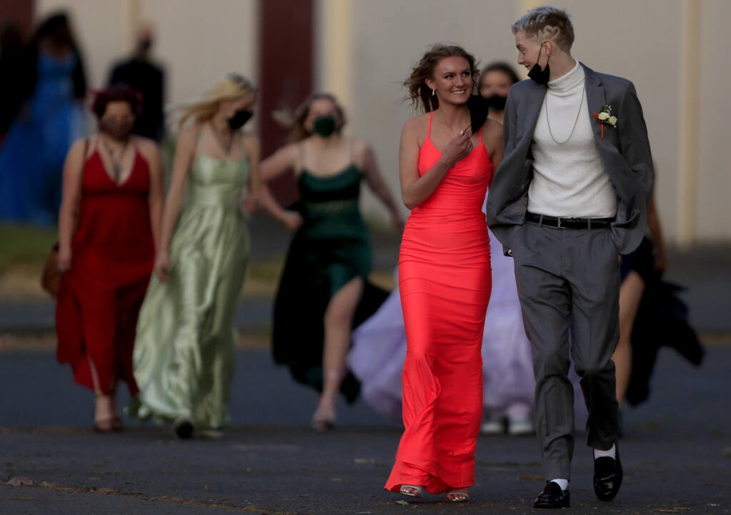 Santa Rosa High School students make the trek across campus to their prom on the school football field, Saturday, May 1, 2021 in Santa Rosa. The students were required to have a negative COVID test or be fully vaccinated.  (Kent Porter / The Press Democrat) 2021