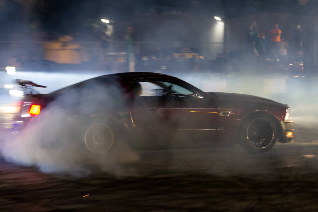 Smoke from a sports car's tires fill the air as its driver spins doughnuts during a sideshow at the Roseland Village Shopping Center in Santa Rosa, California, on Wednesday, Sep. 16, 2020. (Alvin A.H. Jornada / The Press Democrat)