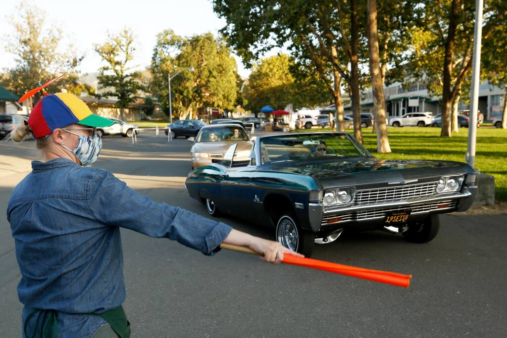 Sonoma County Fairgrounds chief operating officer Kaitlyn Findley-Thorn directs cars into line during the Fair Food Frenzy drive-thru, where county fair afficionados ordered some of their favorite food items, at the Sonoma County Fairgrounds in Santa Rosa on Friday, Aug. 7, 2020. The event was one of the few socially distanced public draws staged by the fair. (Alvin A.H. Jornada / The Press Democrat)