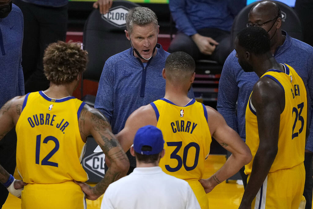 Golden State Warriors coach Steve Kerr, center, talks with his players during a timeout against the Sacramento Kings on Sunday, April 25, 2021, in San Francisco. (Tony Avelar / ASSOCIATED PRESS)