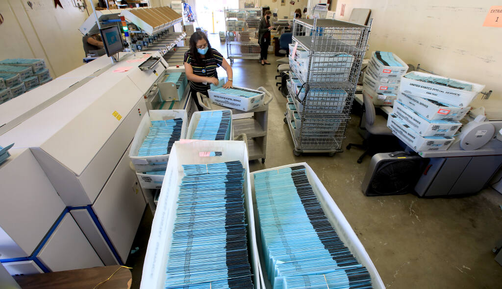 Ibon Suazo, a senior elections specialist with the county, prepares to feed mail in ballots in to signature verification equipment, Wednesday, Nov. 4, 2020 at the Sonoma County Registrar of Voters. (Kent Porter / The Press Democrat) 2020