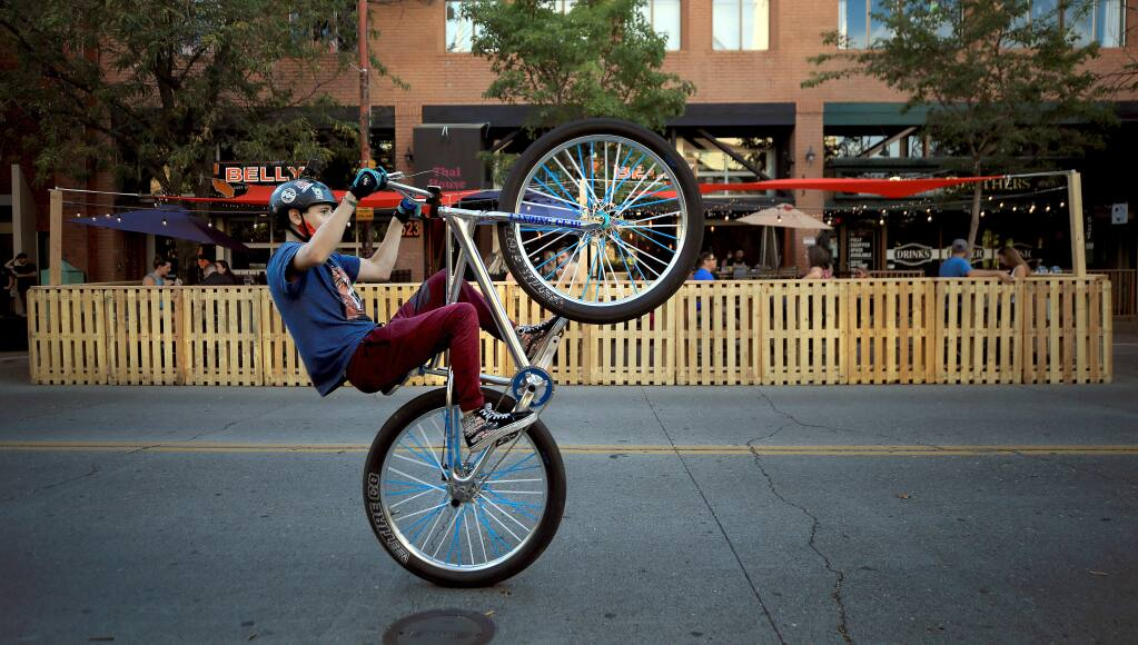 Jonah Feith, 14, of Santa Rosa performs a wheelie on Fourth Street, Friday, July 10, 2020 as he and his friends take advantage of a three-month closure from B Street to E Street. (Kent Porter / The Press Democrat)