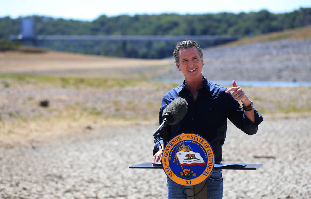 Gov. Gavin Newsom, standing on the dry bed of Lake Mendocino, accounces a drought emergency in Sonoma and Mendocino counties. (KENT PORTER / The Press Democrat)