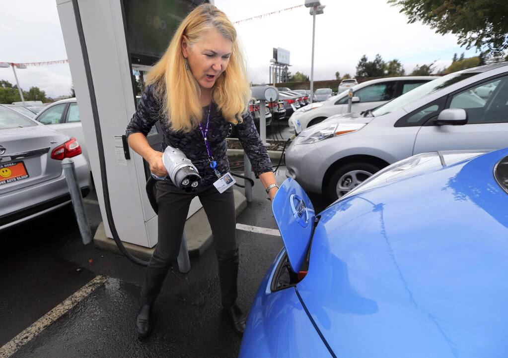 Beth Fulton charges her Nissan Leaf at Jim Bone Nissan in Santa Rosa on October 14, 2016. (John Burgess/The Press Democrat)