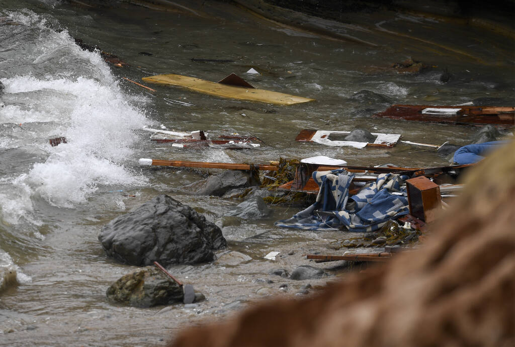 Wreckage and debris from a capsized boat washes ashore at Cabrillo National Monument near where a boat capsized just off the San Diego coast Sunday, May 2, 2021, in San Diego. (AP Photo/Denis Poroy)