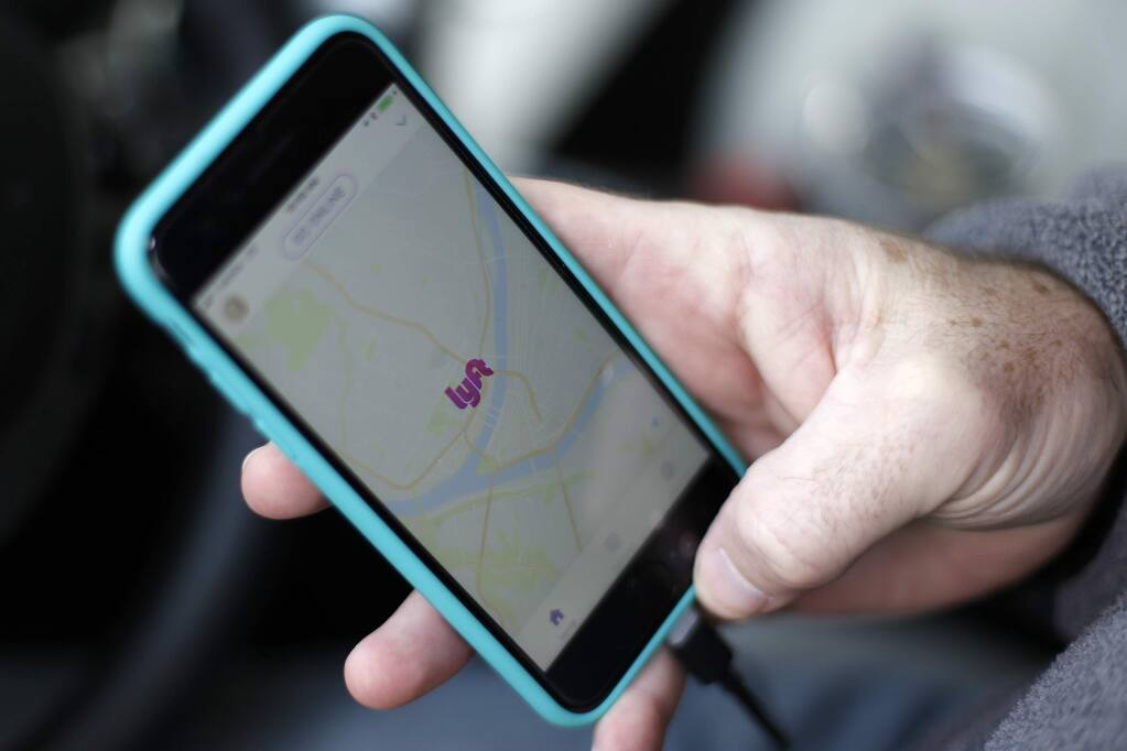 FILE- In this Jan. 31, 2018, file photo, a Lyft driver opens the Lyft app on his phone while waiting for a fare in Pittsburgh. (AP Photo/Gene J. Puskar, File)