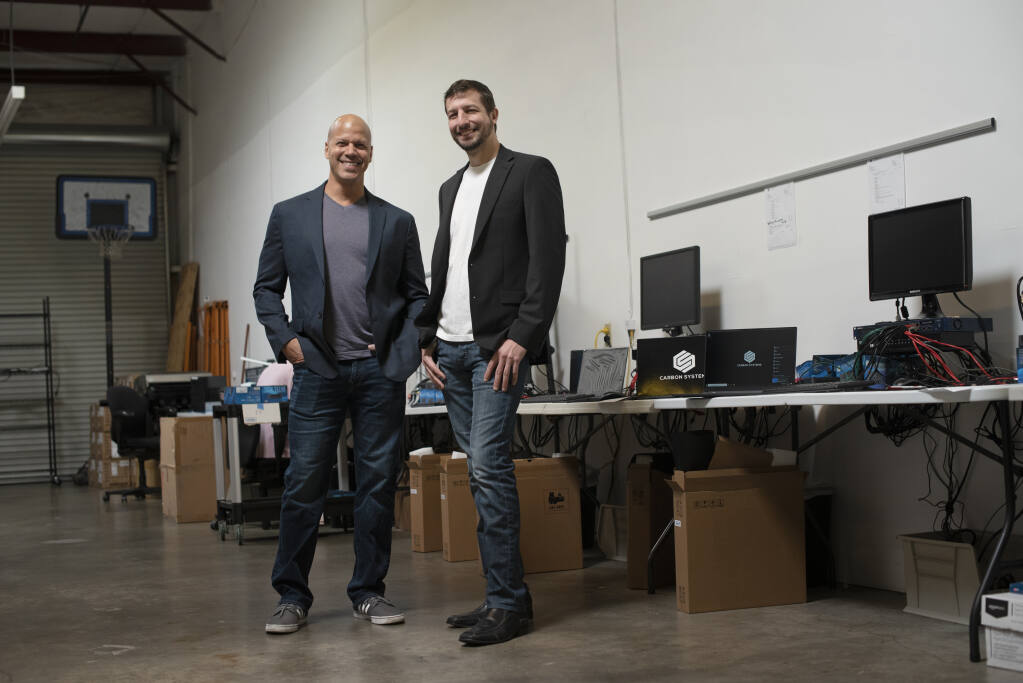 Carbon Systems COO John Rosebaugh, left, and CEO David Cook at the Carbon Systems production warehouse in Santa Rosa on Thursday, March 11, 2021. (Erik Castro / For The Press Democrat)