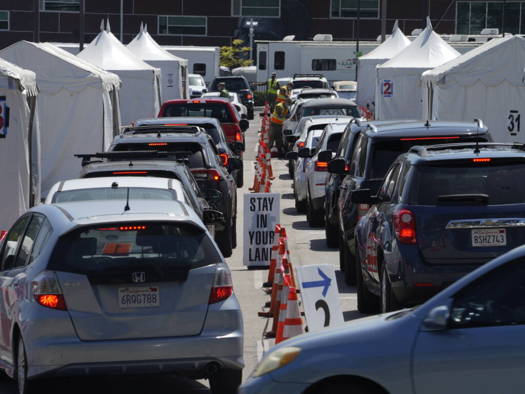 In this April 8, 2021 file photo motorists sit inside their vehicles as they wait their turn to be inoculated with a COVID-19 vaccine at the California State University, Los Angeles campus in Los Angeles. (AP Photo/Damian Dovarganes)