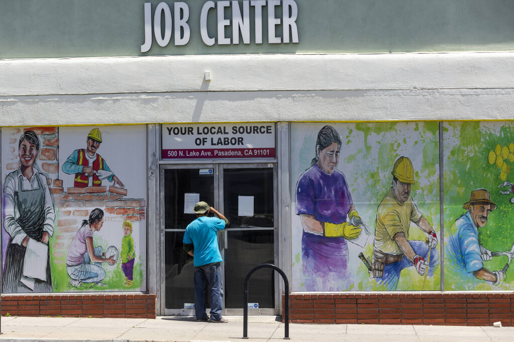 FILE - In this May 7, 2020, file photo, a person looks inside the closed doors of the Pasadena Community Job Center in Pasadena, Calif., during the coronavirus outbreak. California Gov. Gavin Newsom's administration says the massive new federal coronavirus relief bill will pump more than $150 billion into the state's economy. Nearly half of that money will go to Californians directly in the form of $1,400 stimulus checks and expanded unemployment benefits. Another $26 billion will go to the state government. Newsom will announce his plans for the money in mid-May. (AP Photo/Damian Dovarganes, File)
