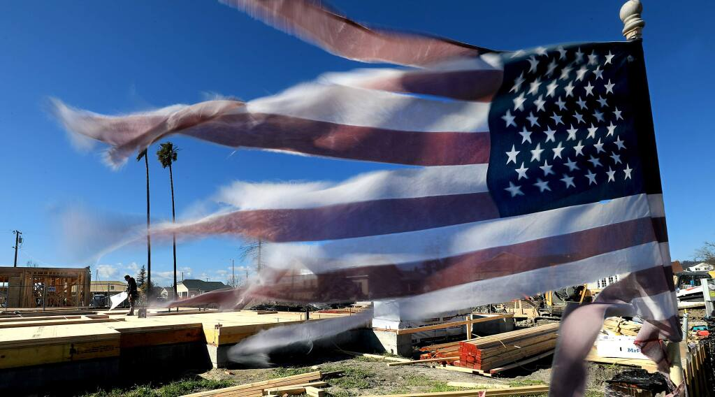 The subfloor of a home on Dogwood Drive is complete as an American Flag, in place since the night of the Tubbs fire, flaps in the breeze, Thursday, Feb. 21, 2019 in Santa Rosa. (Kent Porter / Press Democrat) 2019