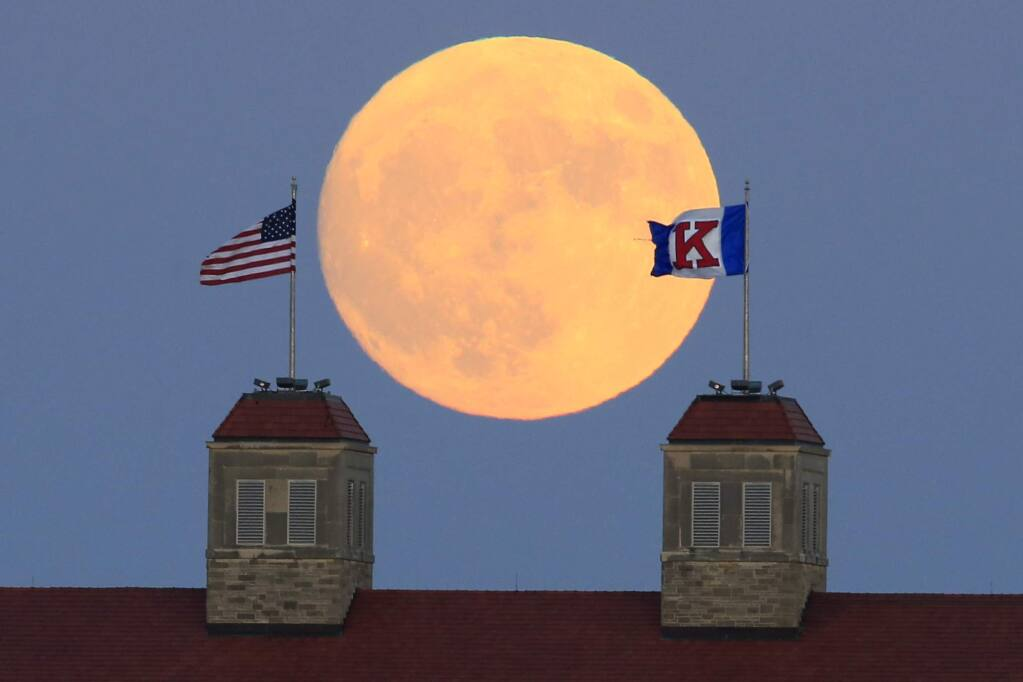 The moon rises beyond flags atop Fraser Hall on the University of Kansas campus in Lawrence, Kan., Sunday, Nov. 13, 2016. Monday morning's supermoon was to be the closest a full moon has been to Earth since Jan. 26, 1948. (AP Photo/Orlin Wagner)