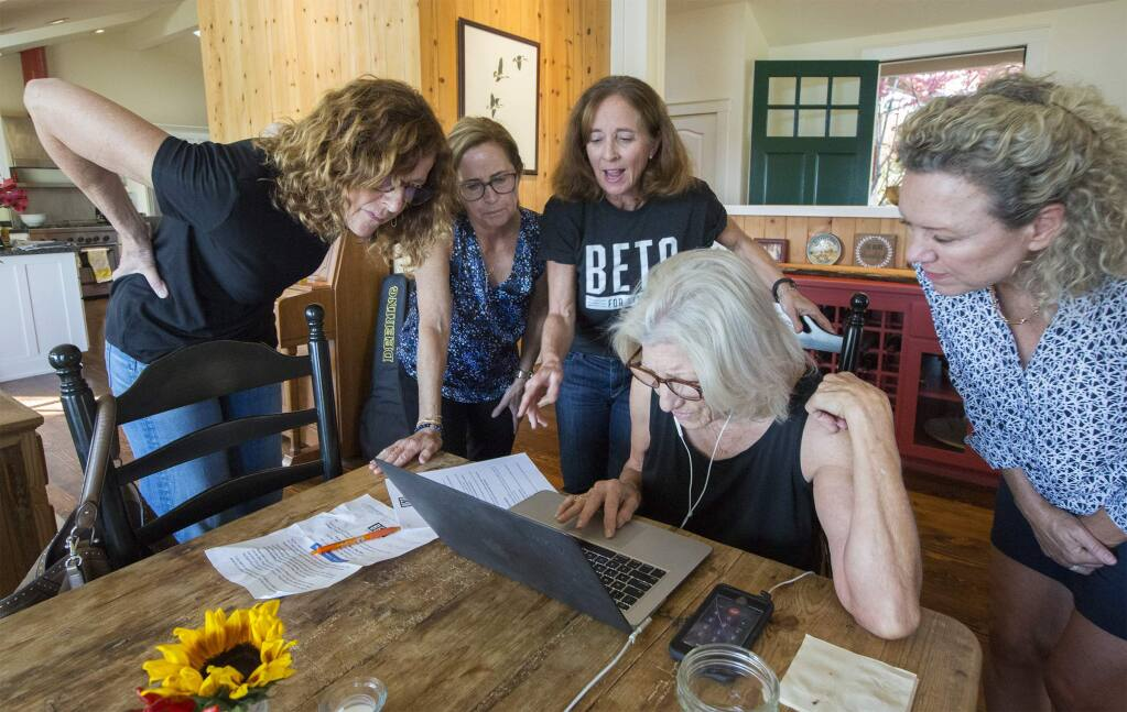 From left, at the Beto O'Rourke phone bank in Glen Ellen are volunteers Jane De Mordant, Patsy Wallace, Laura Stanfield, Ree Whitford and Gail Diserens. Ree is making the first call to a voter in Texas and everyone is gathered around to see how it goes. (Photo by Robbi Pengelly/Index-Tribune)