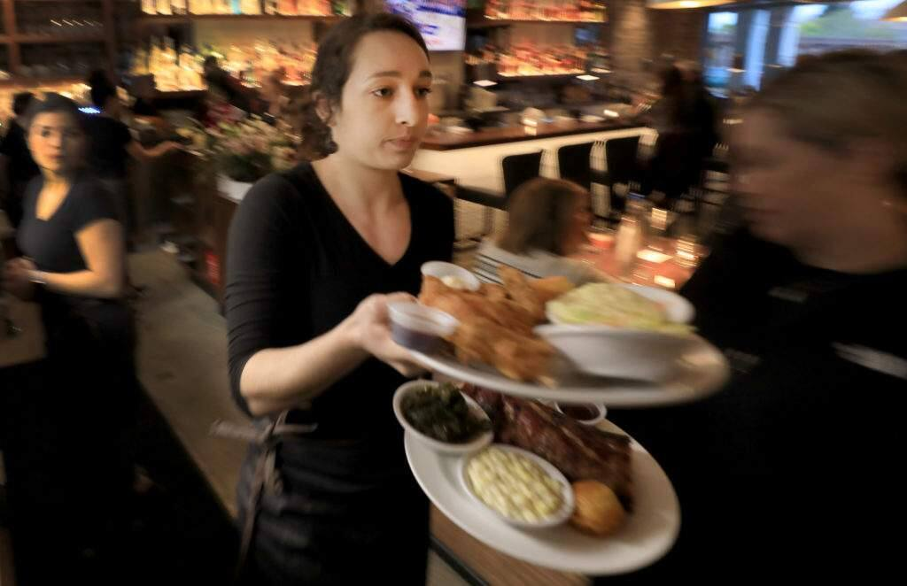 During a soft opening for Sweet T's in Windsor, Monday, March 4, 2019, server Hayley Louzao delivers food to customers. Sweet T's was destroyed during the Tubb's fire as it roared over Fountaingrove and in to Santa Rosa. (Kent Porter / The Press Democrat) 2018