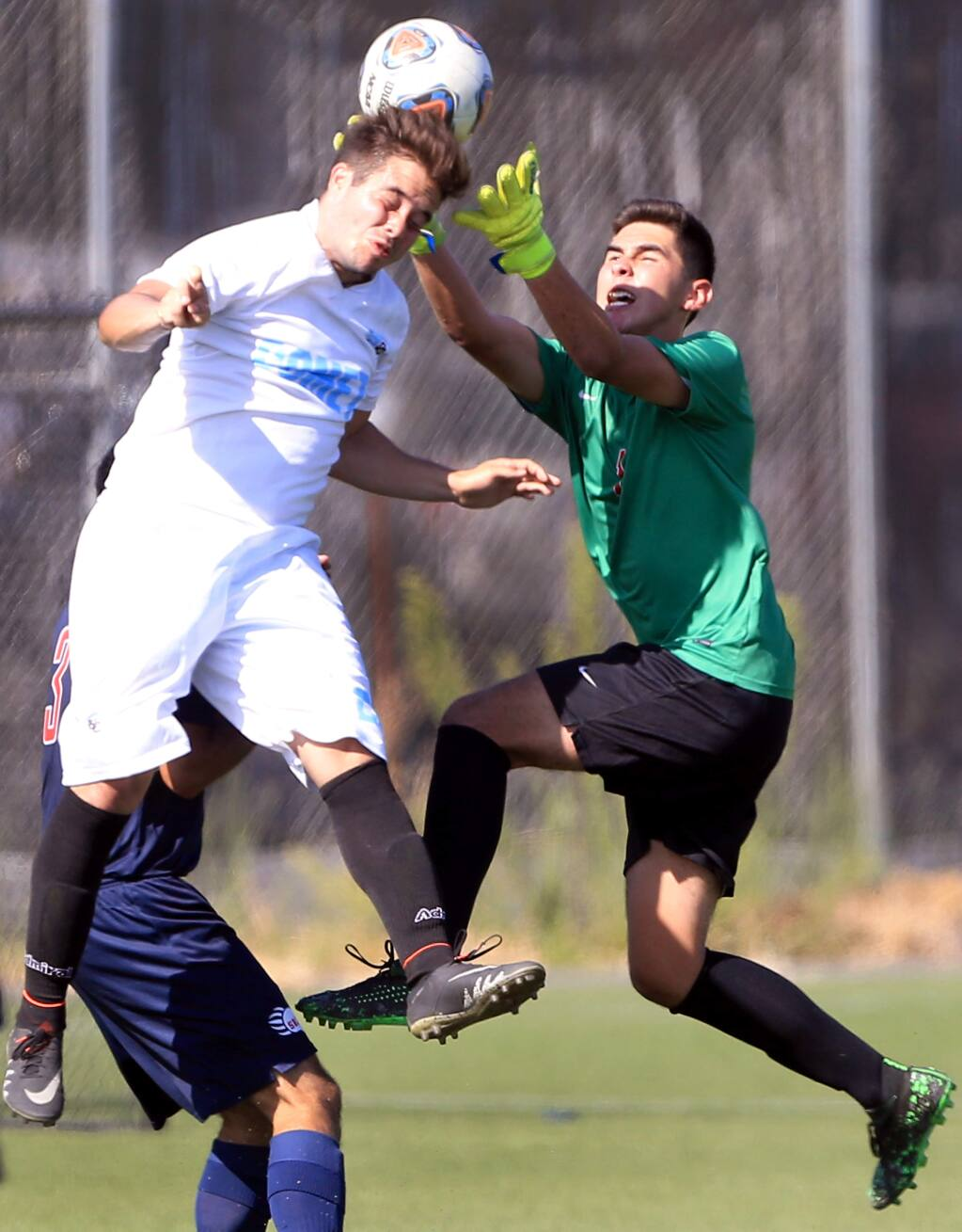 Santa Rosa Junior College goalkeeper Cristian Hernandez makes a save on goal over the header of Contra Costa's Eduardo Torres, during the Bear Cubs' home opening rout of the Comets. (Kent Porter / The Press Democrat)