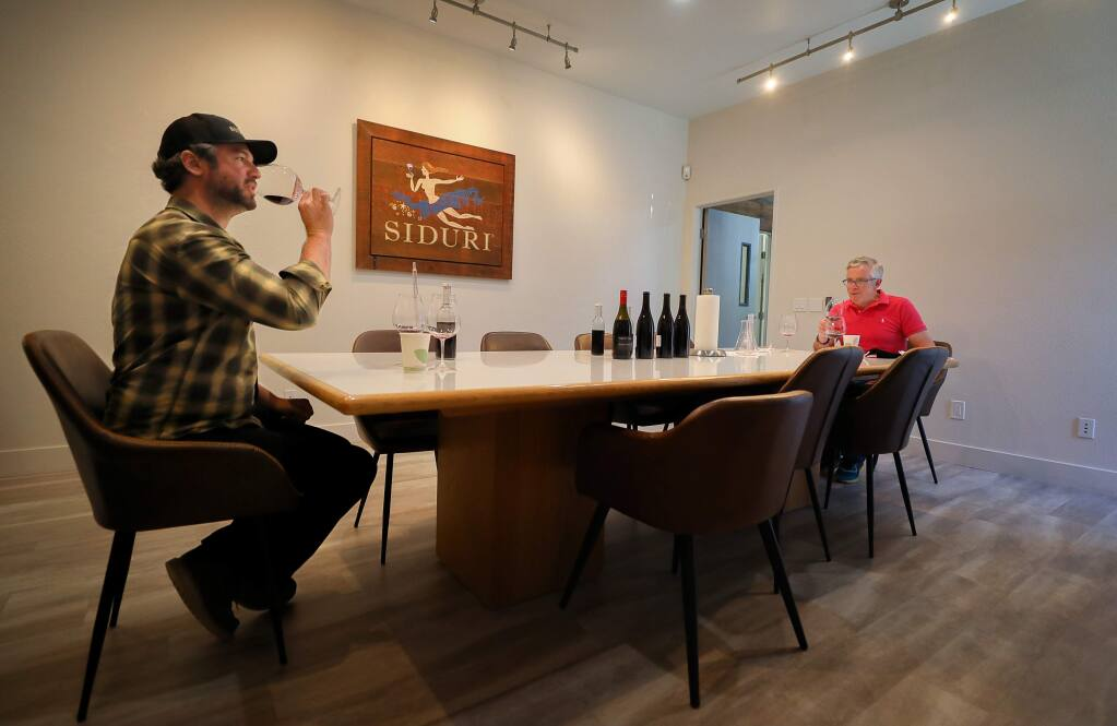 Winemakers Matt Revelette, left, and Adam Lee work on blending wines while maintaining the proper social distance at Siduri Wines, in Santa Rosa on Thursday, June 18, 2020. (Christopher Chung/ The Press Democrat)