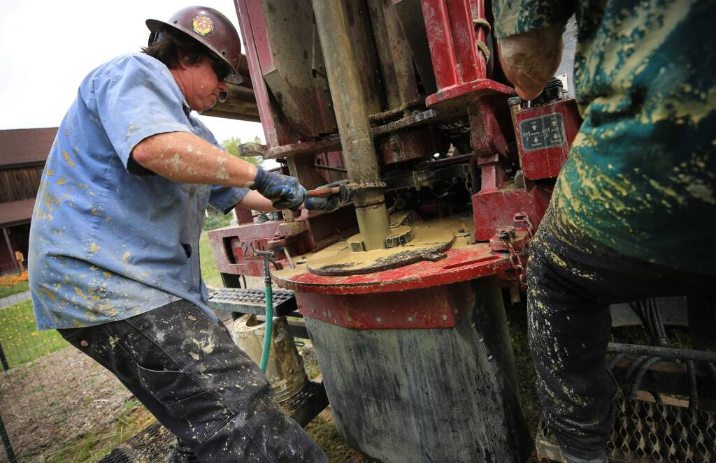 Drake Coffey, left, secures another length of pipe to a water well drill bit as he and Robert Burgess of Weeks Drilling & Pump Co.drill a residential water well near Cotati, Wednesday June 7, 2017. (Kent Porter / The Press Democrat) 2017