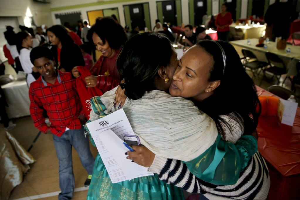 Tsehainesh Abraham, right, hugs Hiwot Kiflay during a luncheon at Roseland Elementary School honoring 10 Eritrean families who lost their homes during the October wildfires. Photo in Santa Rosa, on Sunday, November 19, 2017. (BETH SCHLANKER/ The Press Democrat)