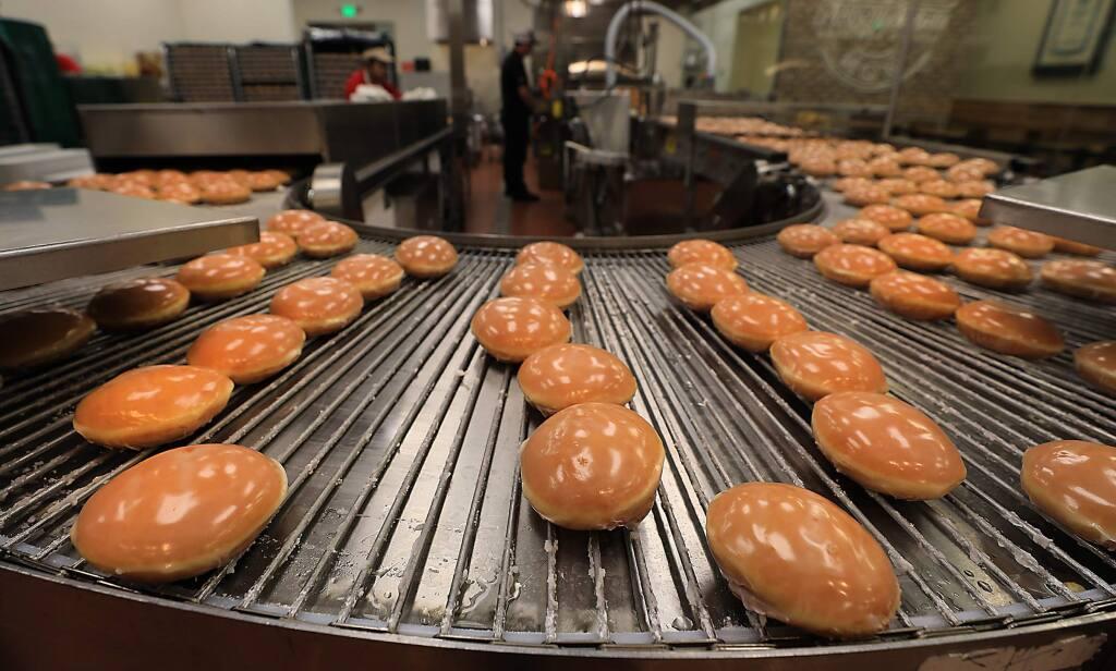 Doughnuts are passed through a glaze prior to the grand opening of Krispy Kreme in Rohnert Park, Monday, Nov. 5, 2018. (Kent Porter / The Press Democrat, 2018)