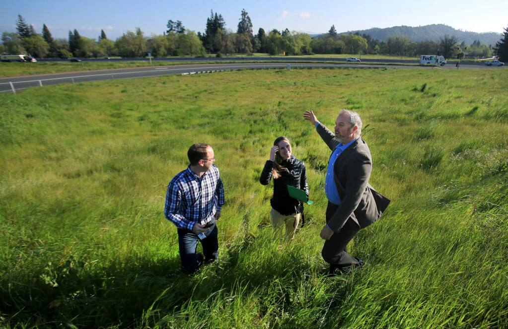 Sonoma County Supervisor James Gore talks with county officials Brad Sherwood and Jennifer Larocque, Thursday March 30, 2017 in Santa Rosa, after Gore did a Facebook live video about the county undertaking a project to replant trees in areas, such as the Airport Boulevard interchange, background, that were removed due to the Highway 101 widening project. (Kent Porter / The Press Democrat) 2017