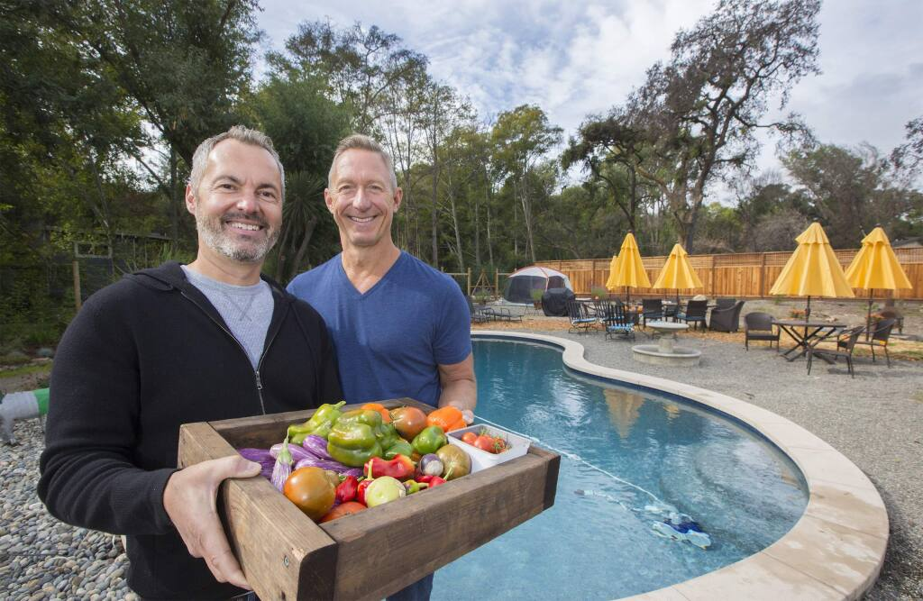 Mike Grace, left, and his husband Steve Thomas with vegetables grown on their O'Donnell Lane property. Their home was completely destroyed by last October's firestorm, but the pool and a few garden boxes were spared. (Photo by Robbi Pengelly/Index-Tribune)