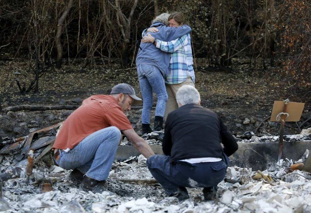 Lenore Hansen, rear left, gets a hug from Kris Black, a volunteer with the Institute of Canine Forensics, as archaeologist Alex De Georgey, left, and Lynee Engelbert, a volunteer with the Institute for Canine Forensics, locate the cremains of her daughter, Erin, who died previously to the Tubbs fire. Photo taken at the rubble of Hansen's home in Santa Rosa, on Sunday, October 29, 2017. (BETH SCHLANKER/ The Press Democrat)