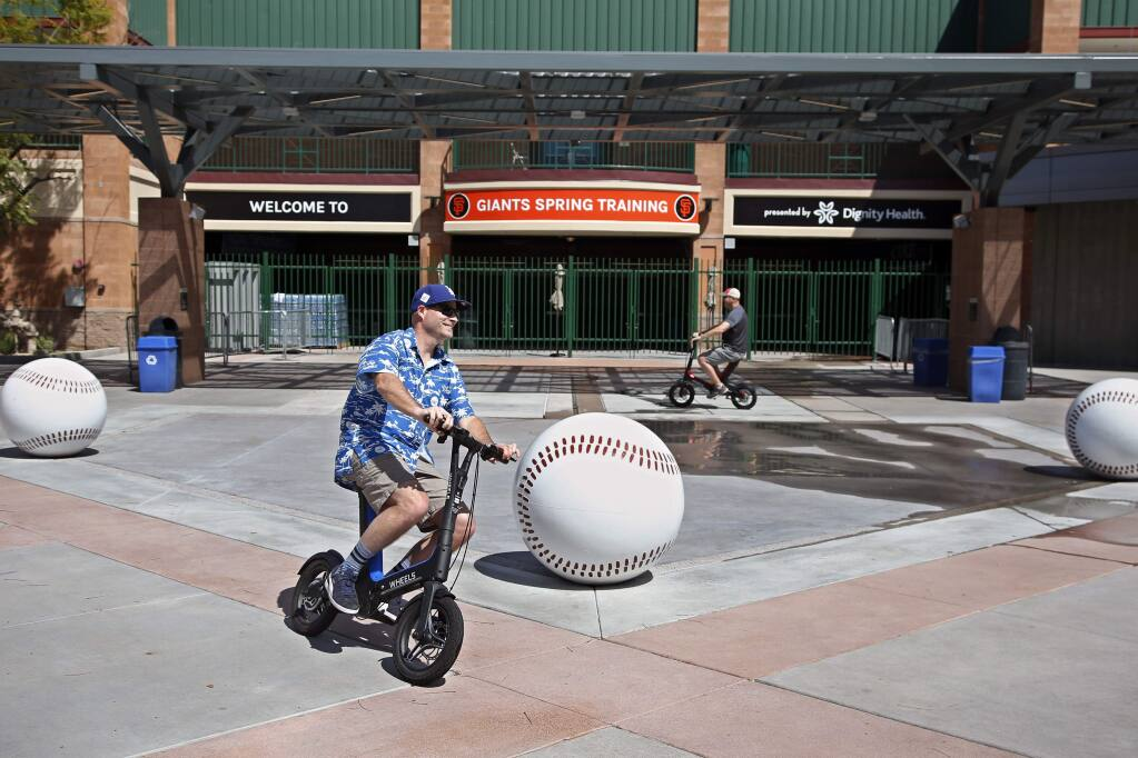 Joe Lieser, left, and Matt Kirmer, right, both of Torrance ride scooters past Scottsdale Stadium, the spring training home of the San Francisco Giants, in Scottsdale, Ariz., Saturday, March 14, 2020. The two came to Arizona with their families to attend spring training games but have not been able to attend any, as the remainder of the exhibitions have been canceled due to coronavirus pandemic. (AP Photo/Sue Ogrocki)