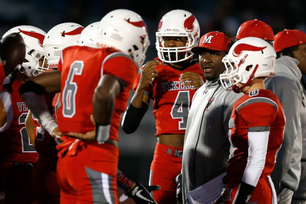 Montgomery head coach Vertis Patton, at right, huddles with his offense before the Vikings' home game against Maria Carrillo High School in Santa Rosa on Friday, Sept. 21, 2018. (Alvin Jornada / The Press Democrat)