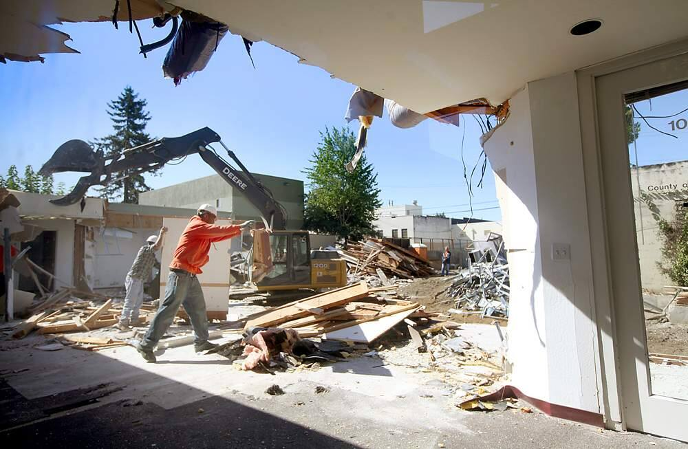 Workers clear debris from a county building being demolished in downtown Santa Rosa, Friday Sept, 5, 2012 to make way for a five-story housing and mixed-use building. (Kent Porter / Press Democrat) 2012
