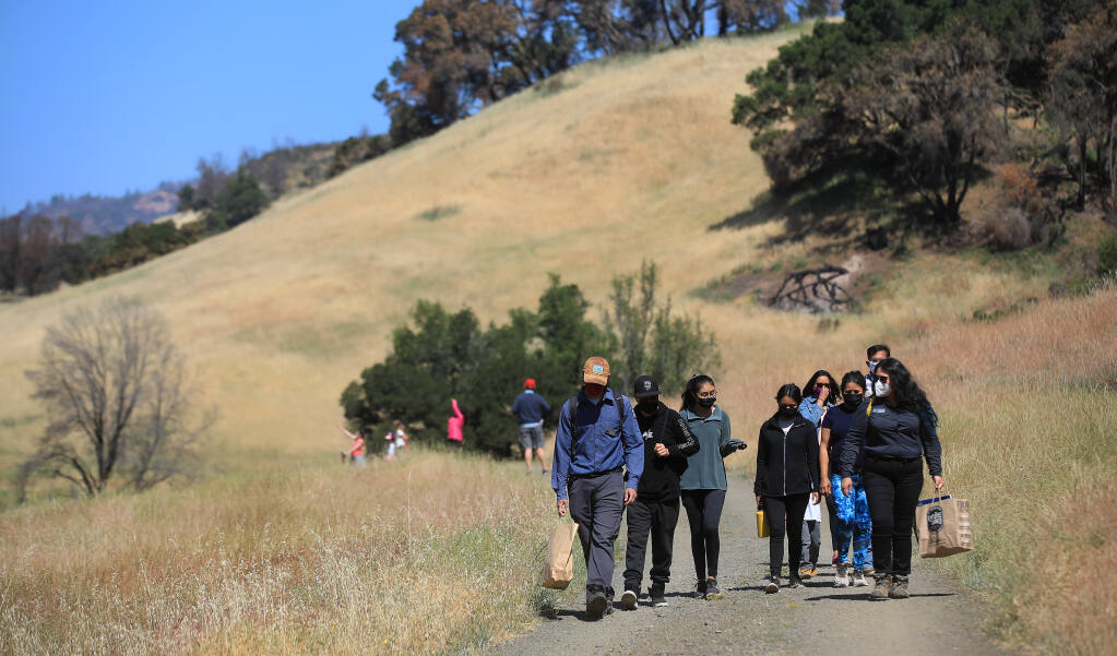 The Hernandez family of Augustine, Rebecca Sarahi and Erica are led on a hike by Mario Coronado, left, and Alma Shaw at Sugarloaf Ridge State Park, part of the Senderos program that aims to introduce the outdoors and nature to Latinos, on Saturday, May 15, 2021. (Kent Porter / The Press Democrat)