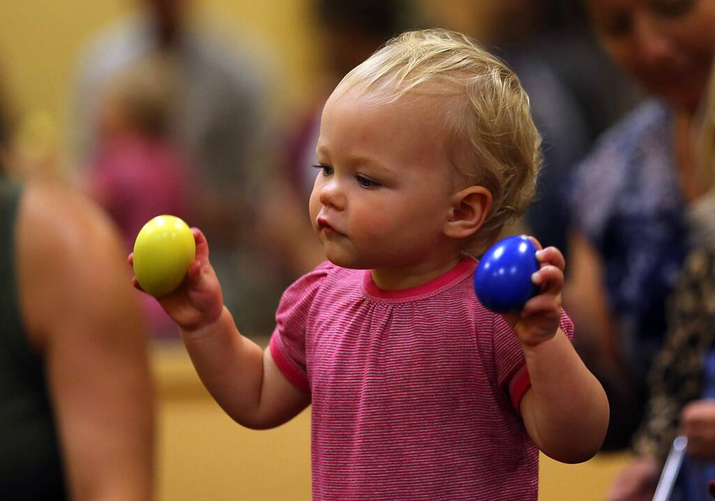 Stella Pile, 15 months, uses the two handed egg shaker method at the Music Together class at Ellington Hall in Santa Rosa. (JOHN BURGESS / The Press Democrat)