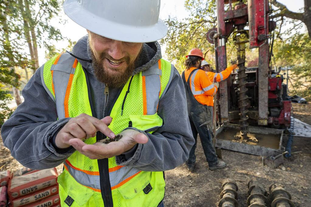 Bryce Russell, with the California Department of Water Resources, checks a sample of soil collected from 20 feet underground as a crew digs a well on Hardies Ln. near Santa Rosa creek on Thursday. (photo by John Burgess/The Press Democrat)