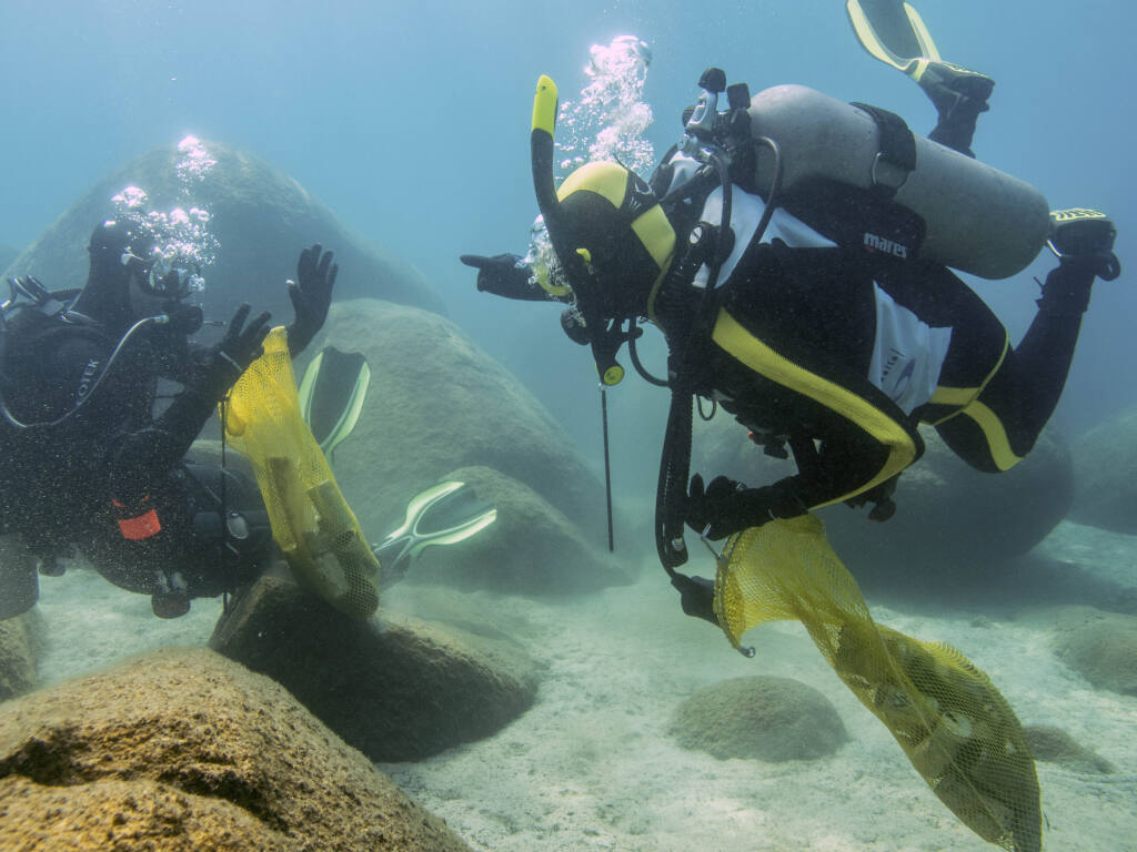 This photo provided by Clean Up The Lake shows a scuba divers beneath the surface of Lake Tahoe, cleaning up trash on Friday, May 14, 2021. A team of scuba divers on Friday completed the first dive of a massive, six-month effort to rid the popular Lake Tahoe of fishing rods, tires, aluminum cans, beer bottles and other trash accumulating underwater. (Clean Up The Lake via AP)