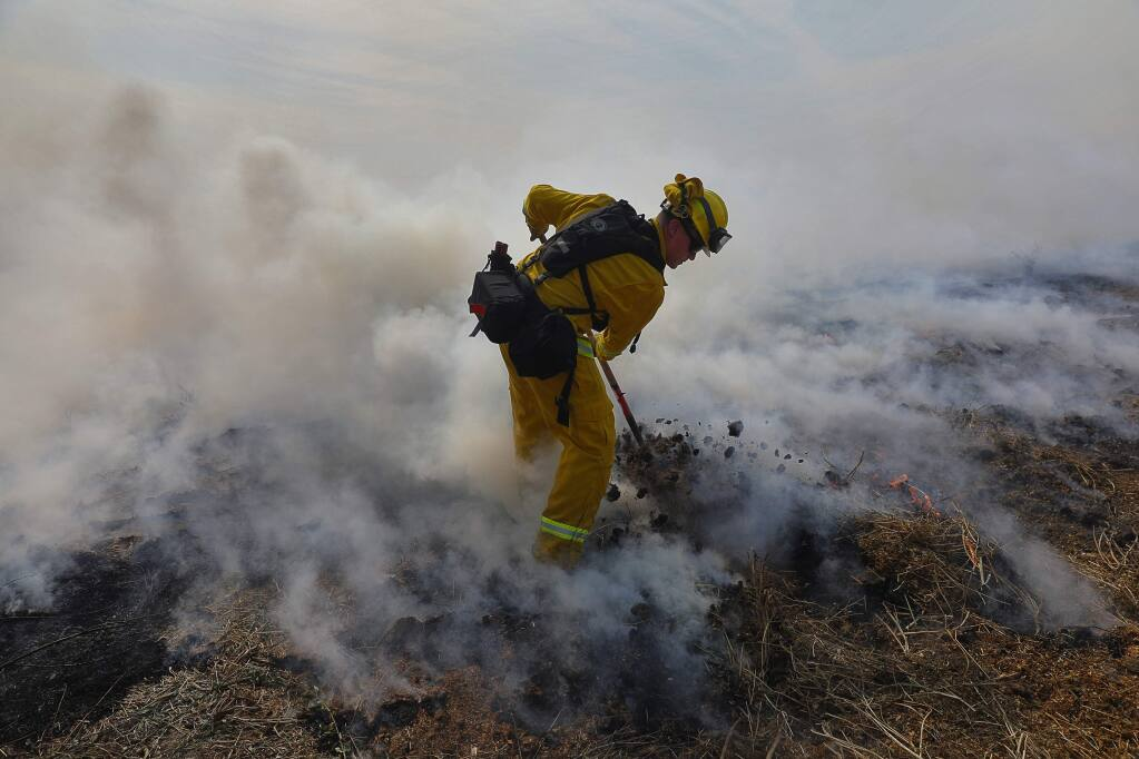 Rancho Adobe firefighter Trevor Steis pulls fuel into a burned area to protect a property along Crane Canyon Road, near Alta Monte Drive, east of Rohnert Park on Wednesday, October 11, 2017. (Christopher Chung/ The Press Democrat)