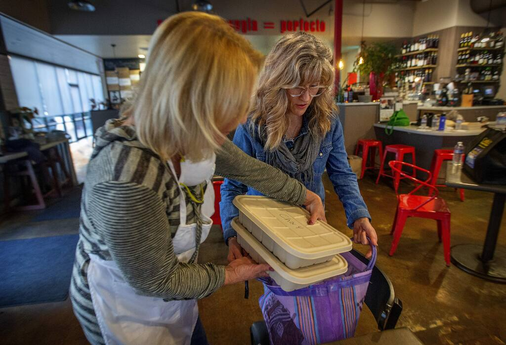 Volunteers loads a chef-made meal from Sonoma Family Meal for Julie Rae Oliver who picks up a weekly meal at Franchetti's restaurant in Santa Rosa. The organization has served over 16,000 meals to victims of the October 2017 wildfires. (photo by John Burgess/The Press Democrat)
