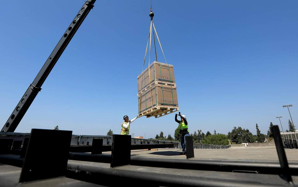 Hardware for the installation of solar panels are lifted to the top of the Fifth Street garage in Santa Rosa, Tuesday August 15, 2017. (Kent Porter / The Press Democrat) 2017