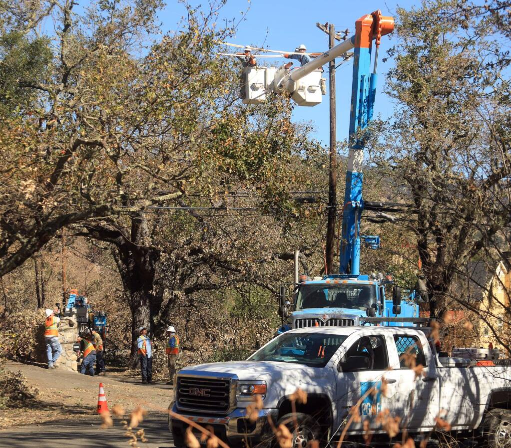 PG&E workers prepare to replace a power pole near the suspected origin of the Tubbs fire on Bennett Lane north of Calistoga, Tuesday Oct. 24, 2017. (Kent Porter / Press Democrat) 2017