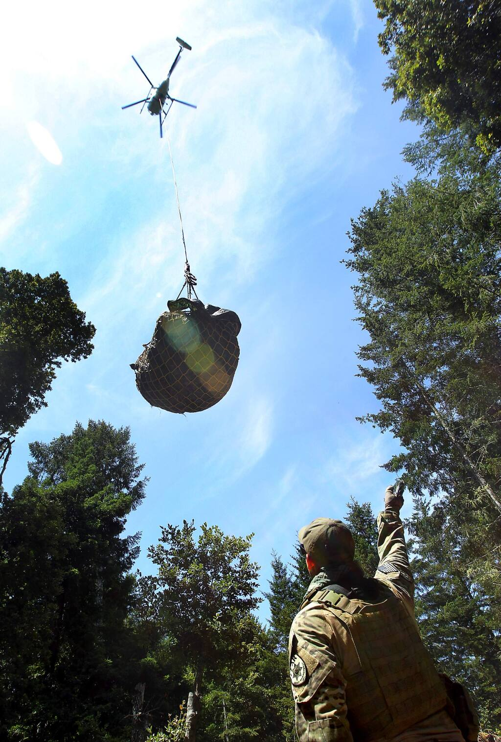 A member of the Lear Asset Management, who refused to give names in fear of retaliation, signals a helicopter leaving with a load of trash taken from a marijuana grow site in the Mendocino Redwood Co. land south of the town of Elk on Saturday, July 19, 2014. (JOHN BURGESS/ PD)