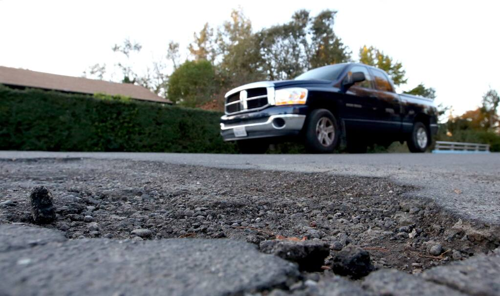 Cars travel along McMinn Ave. near Delport Ave. where drivers have to deal with rough roads, Saturday, November 22, 2014. (Crista Jeremiason / The Press Democrat)