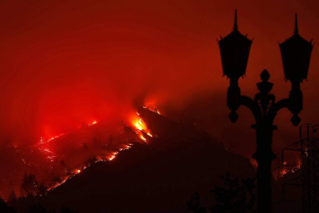 Flames from the Nuns fire are seen at night on a ridgeline adjacent to Ledson Winery in Kenwood, California on Monday, October 16, 2017. (Alvin Jornada / The Press Democrat)
