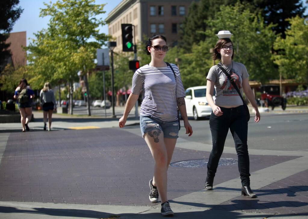 Spencer Morton, right, balances leftovers from dinner on her head as she and her friend Heather Littlefield cross Third St. at Mendocino Ave next to Old Courthouse Square in Santa Rosa, on Sunday, July 13, 2014. (BETH SCHLANKER/ The Press Democrat)