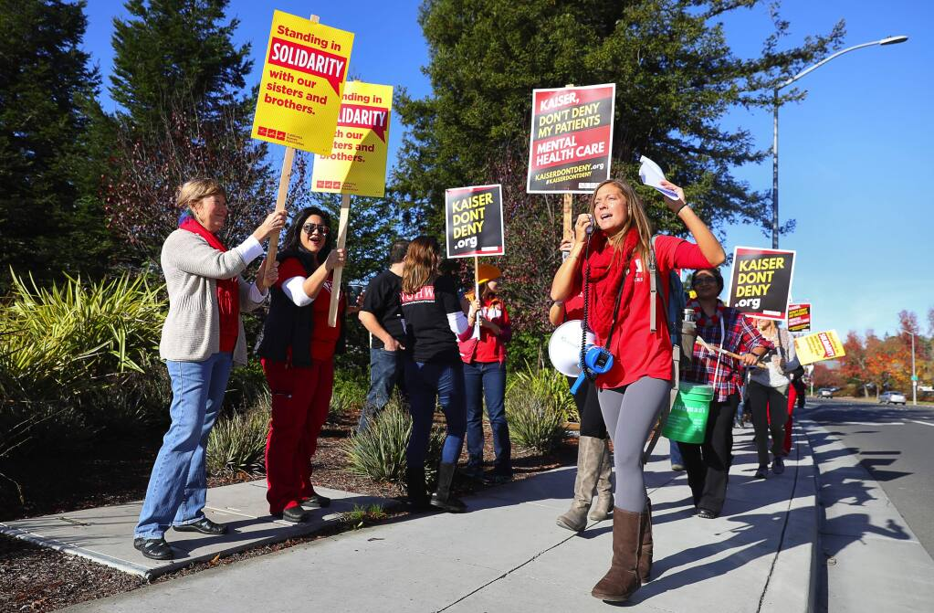Marriage and family therapist Devon Maher, right, leads a chant with striking mental health professionals, along Santa Rosa Avenue, in front of the Kaiser Permanente Santa Rosa Medical Center on Tuesday, December 11, 2018. (Christopher Chung/ The Press Democrat)