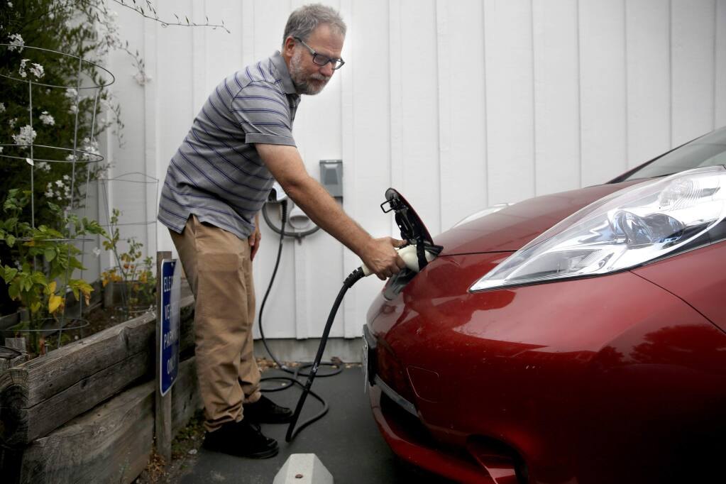 Carl Mears unplugs the charger from his Nissan Leaf electric car at his condo complex before heading to work. Photo taken in Cotati, on Thursday, July 9, 2015. (BETH SCHLANKER/ The Press Democrat)
