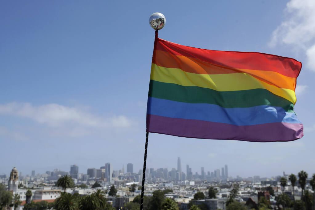 A rainbow flag set up by Ronnie Alvarez, lead designer of Balloon Magic, flies over the skyline at Dolores Park in San Francisco, Sunday, June 28, 2020. (AP Photo/Jeff Chiu)