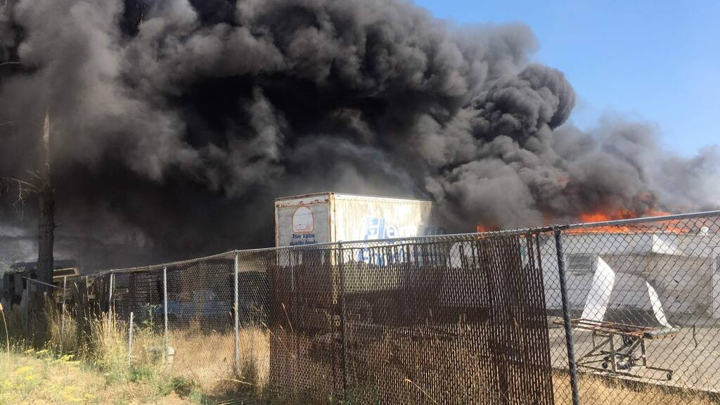 A trailer fire that started on private property on Scenic Avenue just outside the city limits of Santa Rosa emits plumes of black smoke on Monday, Aug. 19, 2019. (KENT PORTER/ PD)