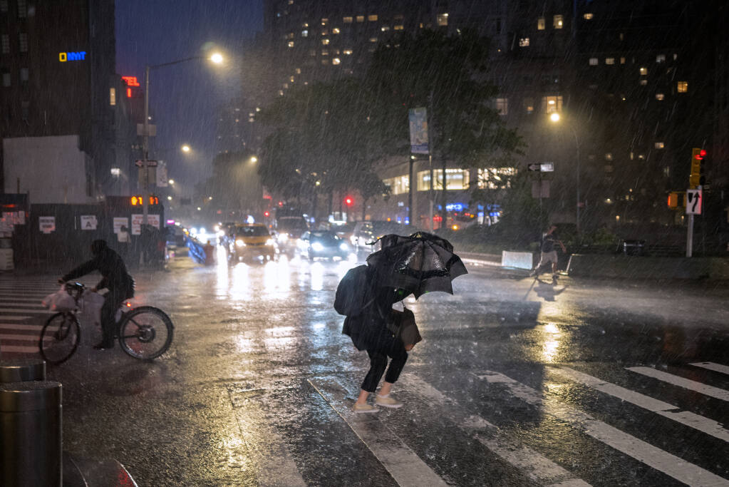 Pedestrians take cover near Columbus Circle in New York Wednesday, Sept. 1, 2021, as the remnants of Hurricane Ida remained powerful while moving along the Eastern seaboard. (AP Photo/Craig Ruttle)