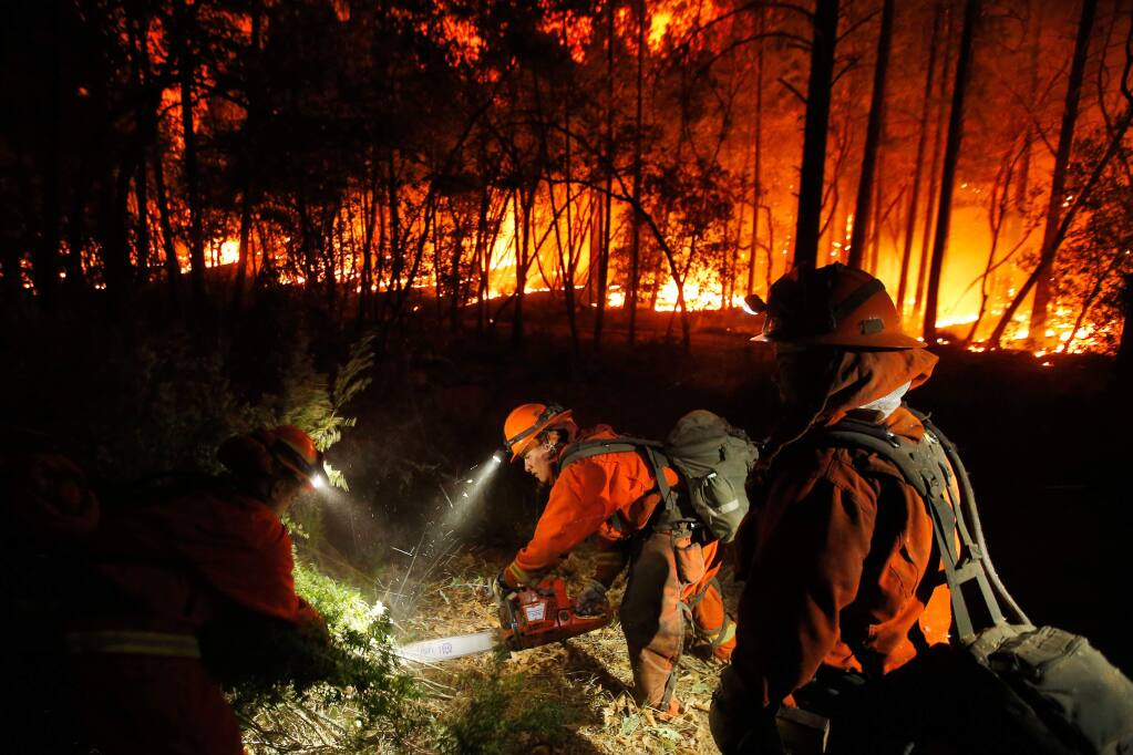 Inmate Jose Jimenez, center, of Cal Fire Mt. Bullion Crew 2, cuts down roadside vegetation with his chainsaw while other inmate crewmembers pull the loose brush away, at the Oakmont fire off Highway 12 in Santa Rosa, California on Tuesday, October 17, 2017. (Alvin Jornada / The Press Democrat)
