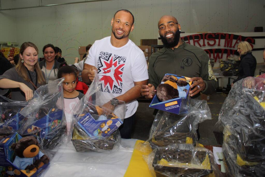 Christina Brunette Hoffemeger, far left, Oakland Raiders alumnus Lorenzon Alexander and DeAngelo Hall, a 13-year veteran of the Washington Redskins, joined hundreds of volunteers packing 3,500 Super Baskets of Hope to be distributed to Northern California hospitalized kids. (Gary Quackenbush / North Bay Business Journal)